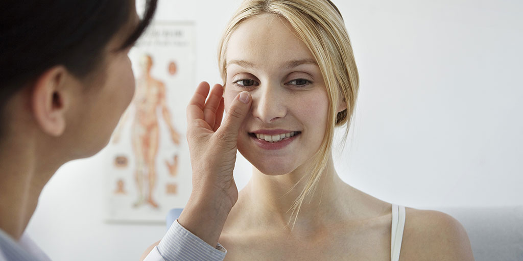 Dermatologist checking woman's face