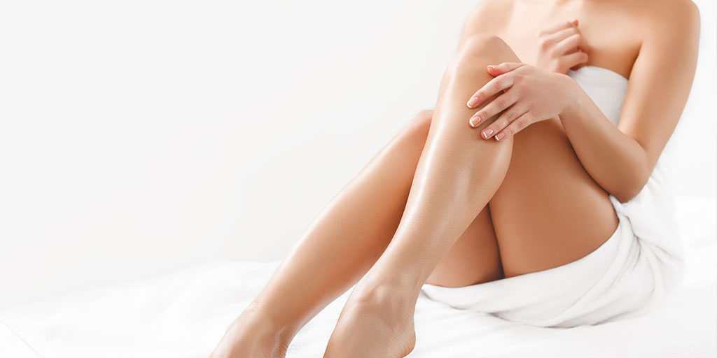 Woman in towel touching her smooth leg